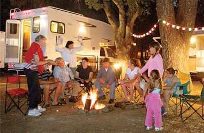 Image of family gathered around campfire at their campsite