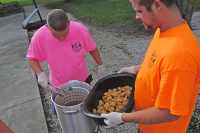 Image of 2 men frying fish